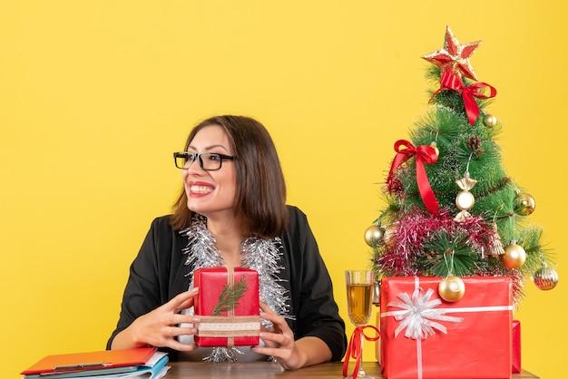 Señora de negocios sonriente en traje con gafas mostrando su regalo mirando algo y sentado en una mesa con un árbol de navidad en la oficina