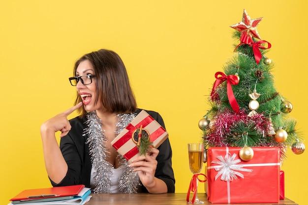 Señora de negocios sorprendida en traje con gafas sosteniendo su regalo y sentada en una mesa con un árbol de navidad en la oficina
