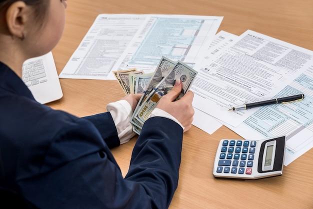 Señora de negocios trabaja con dólares y documentos fiscales 1040