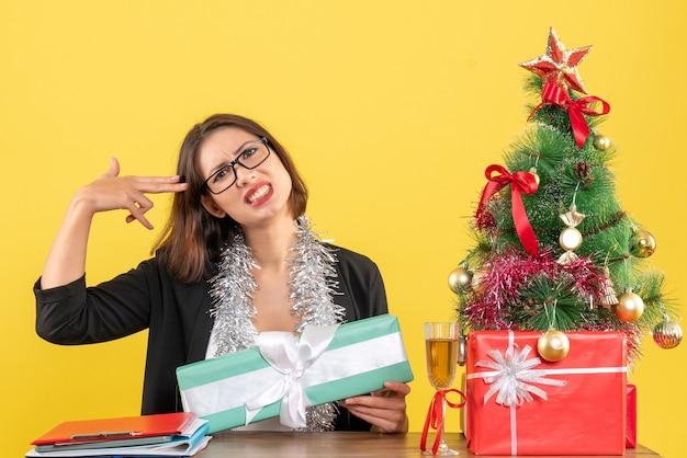 Señora de negocios en traje con gafas mostrando su regalo confundida por algo y sentada en una mesa con un árbol de navidad en la oficina