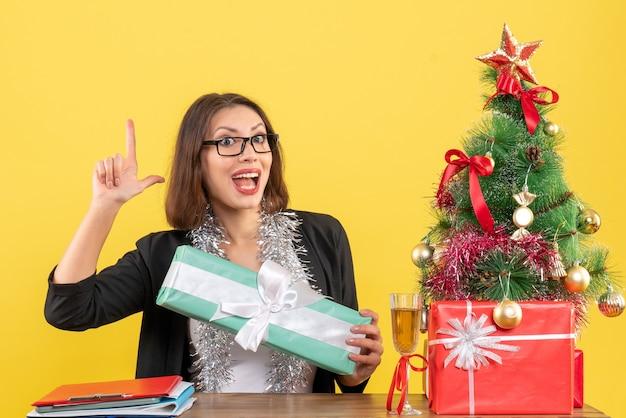 Señora de negocios en traje con gafas mostrando su regalo sintiéndose feliz y sentada en una mesa con un árbol de navidad en la oficina