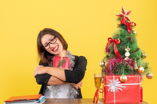 Señora de negocios en traje con gafas mostrando su regalo soñando con algo y sentado en una mesa con un árbol de navidad en la oficina