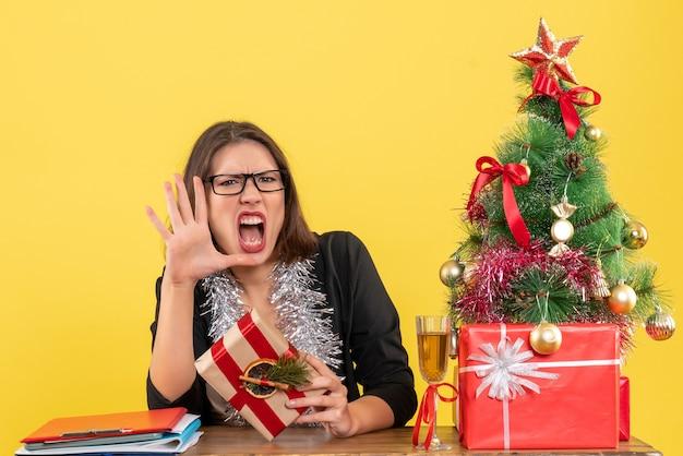Señora de negocios en traje con gafas sosteniendo su regalo gritando a alguien y sentada en una mesa con un árbol de navidad en la oficina