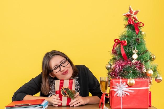 Señora de negocios en traje con gafas sosteniendo su regalo y soñando con algo sentado en una mesa con un árbol de navidad en la oficina