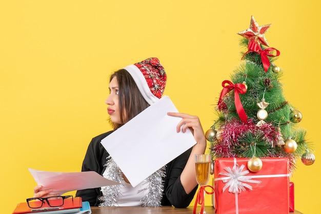 Señora de negocios en traje con sombrero de santa claus y adornos de año nuevo sintiéndose confundida y sentada en una mesa con un árbol de navidad en la oficina