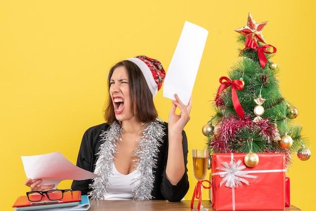 Señora de negocios en traje con sombrero de santa claus y adornos de año nuevo sintiéndose nerviosa y sentada en una mesa con un árbol de navidad en la oficina