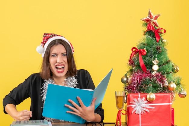 Señora de negocios en traje con sombrero de santa claus y decoraciones de año nuevo comprobando el documento sintiéndose nerviosa y sentada en una mesa con un árbol de navidad en la oficina