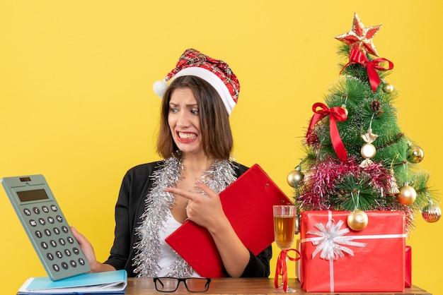 Señora de negocios en traje con sombrero de santa claus y decoraciones de año nuevo sintiéndose confundida mirando calculadora y sentada en una mesa con un árbol de navidad en la oficina