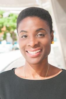 Señora negra feliz positiva que presenta al aire libre y que sonríe