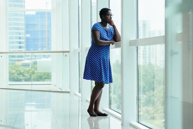 Señora negra con vestido de lunares de pie en la oficina y mirando por la ventana alta
