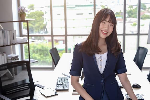 La señora de la oficina es hermosa, cabello largo, negro y feliz asiática con un traje azul oscuro en la oficina moderna con un escritorio y grandes ventanales que difuminan el fondo.