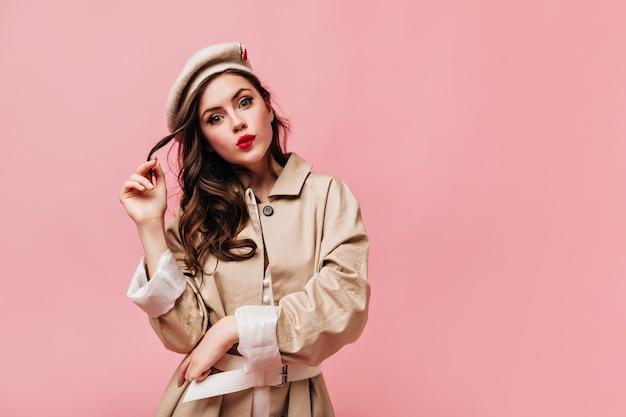 Señora de ojos verdes con lápiz labial rojo juega cabello. mujer con abrigo beige y sombrero se muerde el labio.