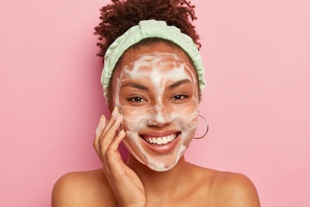 Señora optimista usa limpiador espumoso para lavarse la cara, sonríe suavemente, se para desnuda, muestra los hombros desnudos