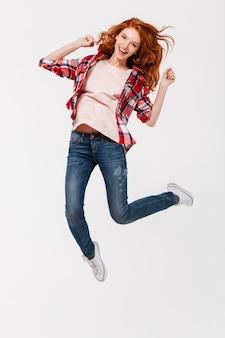 Señora pelirroja joven feliz saltando aislado