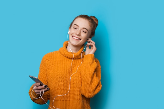 Señora pelirroja con pecas escuchando música con teléfono y auriculares está planteando en una pared azul