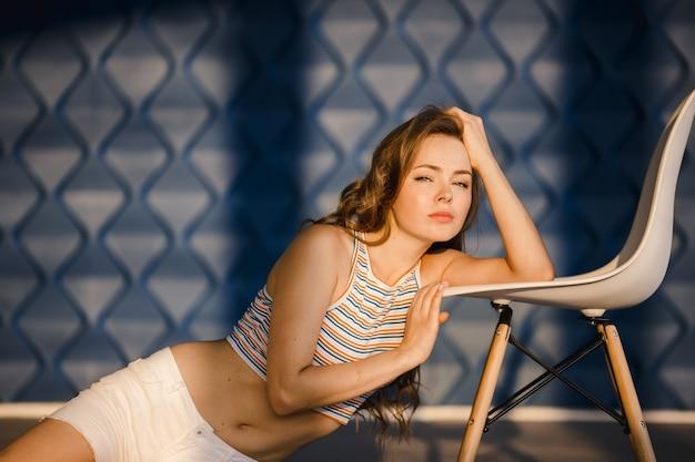 Señora con el pelo ondulado miente en la silla blanca antes de una pared azul
