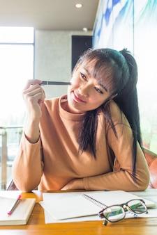 Señora de pensamiento con la pluma en la mesa