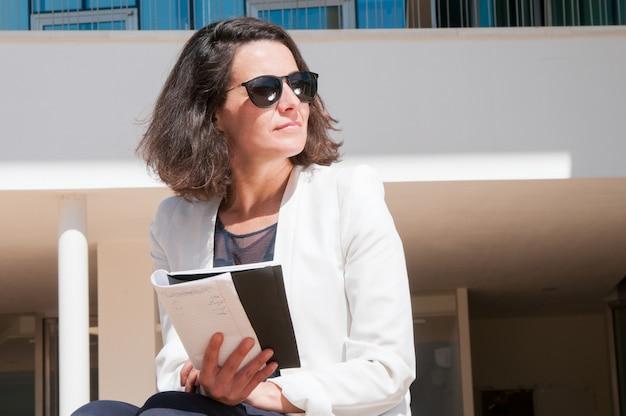 Señora pensativa del negocio que lee sus notas