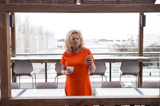 Señora pensativa con smartphone tomando café