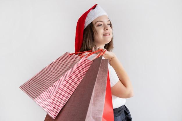 Señora pensativa sonriente que sostiene bolsos de compras en hombro