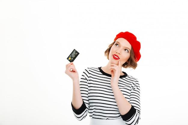 Señora pensativa con tarjeta de crédito y mirando hacia arriba