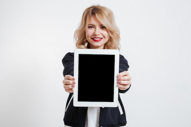 Señora de pie sobre fondo blanco que muestra la pantalla de la tableta