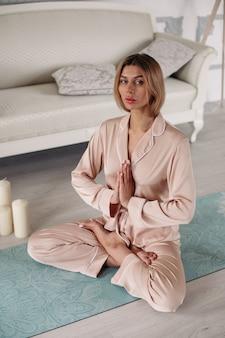 Señora en pijama practica yoga y sentada en pose especial en la alfombra en casa