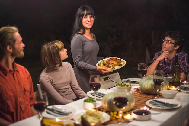 Señora con plato junto a mesa con gente