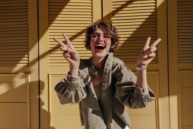 Señora positiva en gafas de sol rosas riendo en puertas amarillas. mujer de pelo corto con chaqueta verde oliva mostrando signos de paz en puertas amarillas.