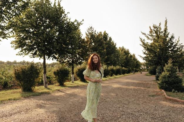 Señora positiva con el pelo rojo y una venda negra en el cuello con un vestido verde largo sonriendo y sosteniendo una copa con champán en la pared de la carretera
