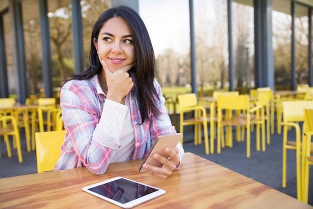 Señora positiva que usa la tableta y el teléfono inteligente en café al aire libre