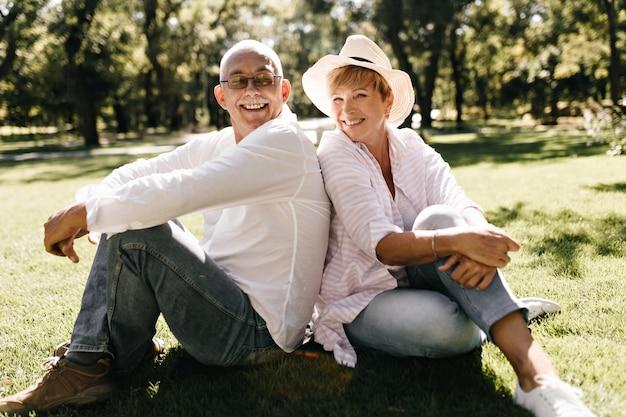 Señora positiva con sombrero fresco en blusa elegante a rayas y jeans sonriendo y sentado en la hierba con el hombre en anteojos y camisa ligera al aire libre.