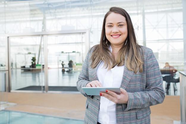 Señora positiva con la tableta que presenta en centro de negocios