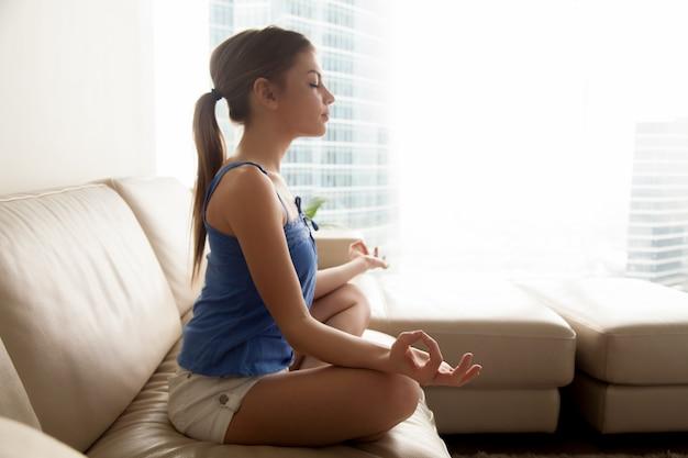 Señora practicando yoga y relajandose en casa