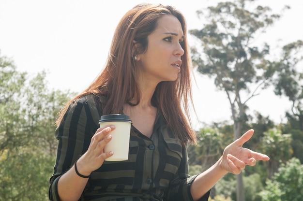 Señora preocupada tomando café en el parque