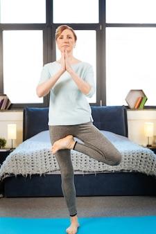 Señora que tiene ejercicios. mujer pacífica con el pelo atado de pie sobre una alfombra azul y haciendo yoga mientras conecta las manos