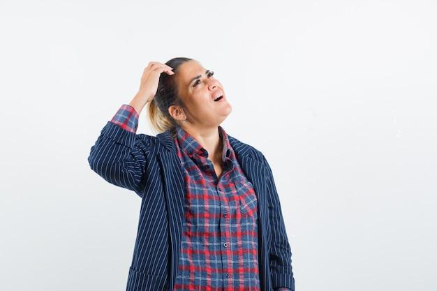 Señora rascándose la cabeza en camisa, chaqueta y mirando olvidadiza. vista frontal.