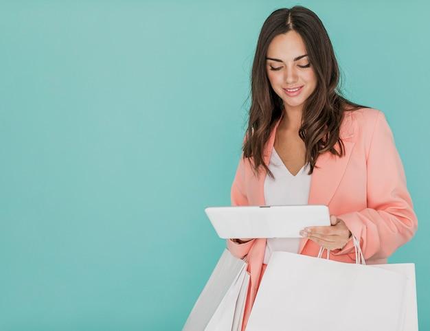 Señora con redes de compras y tableta sobre fondo azul.