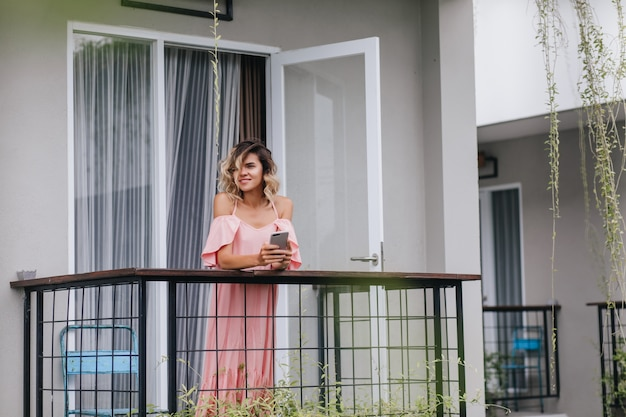 Señora rizada glamorosa de pie en el balcón con smartphone. encantadora chica caucásica mirando la ciudad desde la terraza.