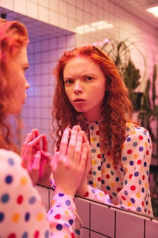 Señora rizada pelirroja de pie cerca del espejo