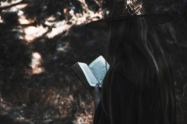 Señora en ropa de bruja leyendo libro