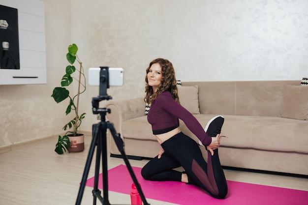Señora en ropa deportiva haciendo yoga y viendo la clase de yoga en línea en una alfombra rosa en casa
