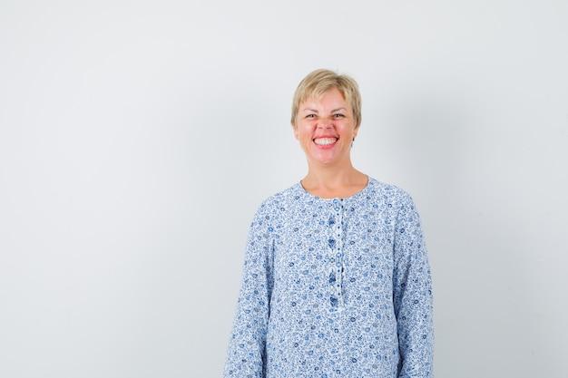 Señora rubia en blusa estampada sonriendo y mirando alegre, vista frontal. espacio para texto