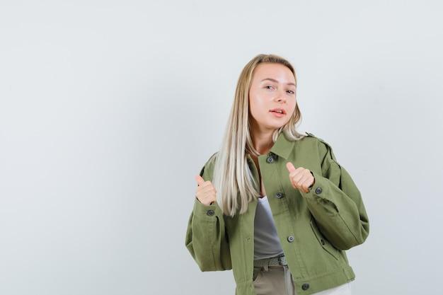 Señora rubia con chaqueta, pantalones apuntando a un lado con los pulgares hacia arriba y mirando confiada, vista frontal.