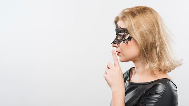 Señora rubia joven en máscara con el dedo cerca de los labios