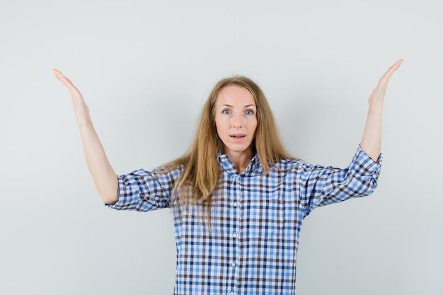 Señora rubia levantando los brazos en camisa y mirando asombrado.