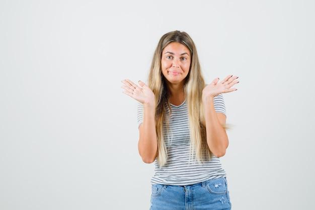 Señora rubia mostrando las palmas en gesto de rendición en camiseta a rayas, jeans y mirando confundido. vista frontal.