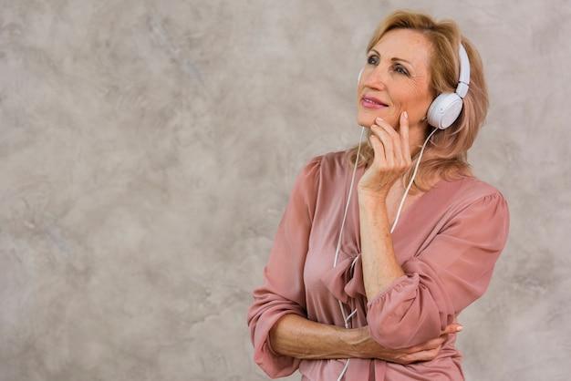Señora rubia sonriente escuchando música en auriculares con espacio de copia