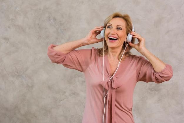 Señora rubia sonriente escuchando música en el set de auriculares