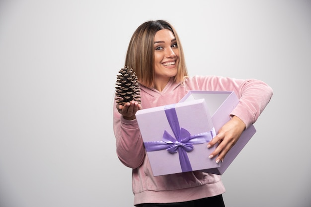 Señora rubia con sudadera rosa saca un cono de roble de la caja de regalo y se siente feliz.